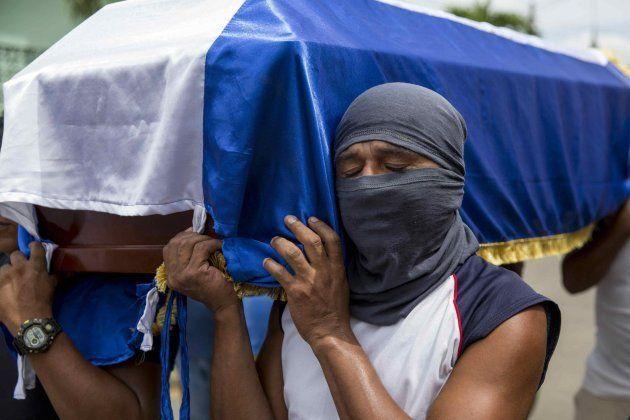 Un hombre llora mientras lleva el ataúd de José Medina, muerto durante las