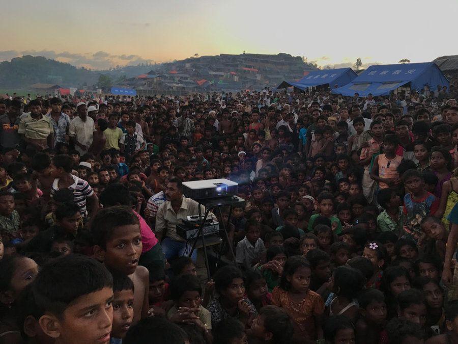 'Desplazados'. Niños rohingya viendo una película de concienciación sobre salud e higiene cerca de un...