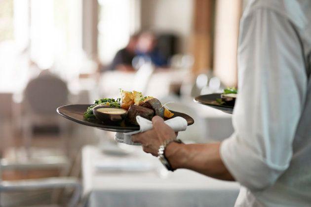 Un camarero lleva platos de comida a una