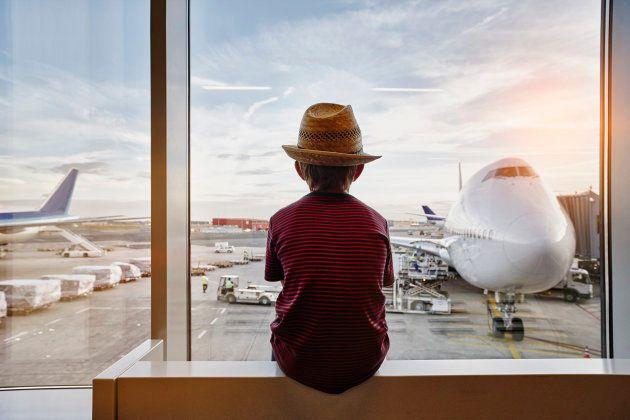 Un niño mira a los aviones a través de la ventana del