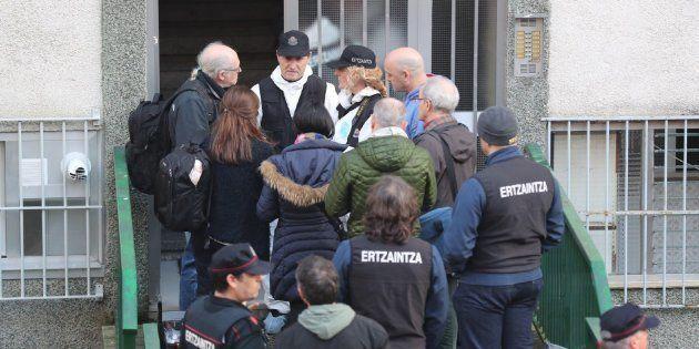 Miembros de la Ertzaintza y vecinos en la puerta del bloque en el que fueron aseinados Rafael y