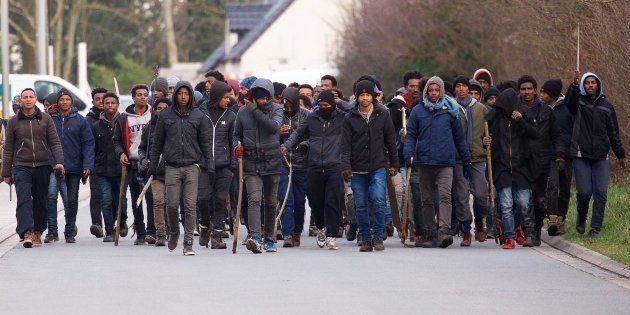 Un grupo de inmigrantes carga palos y piedras durante un enfrentamiento cerca del puerto de