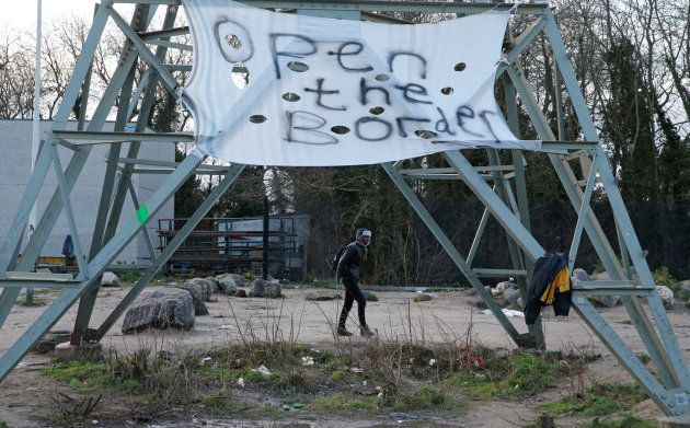 Un migrante en Calais pasa junto a un cartel en el que puede leerse