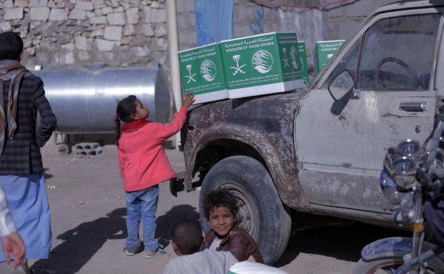Una niña yemení acaricia una caja de ayuda alimentaria enviada por Arabia