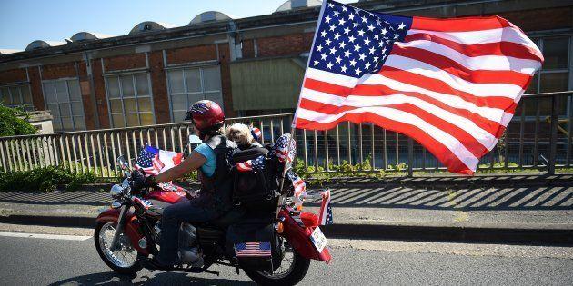 Un motero en una harley con una bandera de Estados