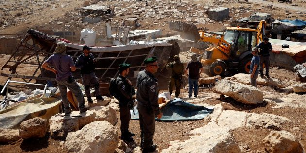 Un grupo de soldados de Israel observan cómo una excavadora tira el poblado de beduinos palestinos de...