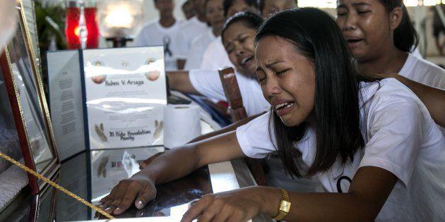 Jessel Mae Arzaga, hija del activista ambiental Rubén Arzaga, llora sobre el féretro de su padre, asesinado...