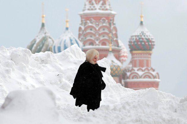 Una mujer se abre camino entre la montaña de nieve que cubre la Plaza Roja de Moscú este