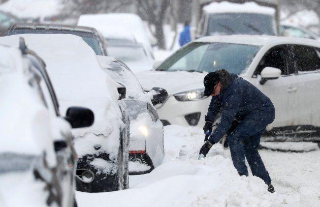 Un hombre retira con una pala la nieve que bloquea su coche en una calle de Moscú este