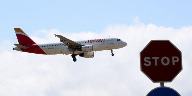 Un avión de Iberia vuela sobre una señala de stop al acercarse al aeropuerto de El Prat en