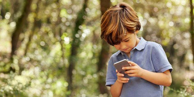 Un niño consulta un teléfono móvil, en una imagen de