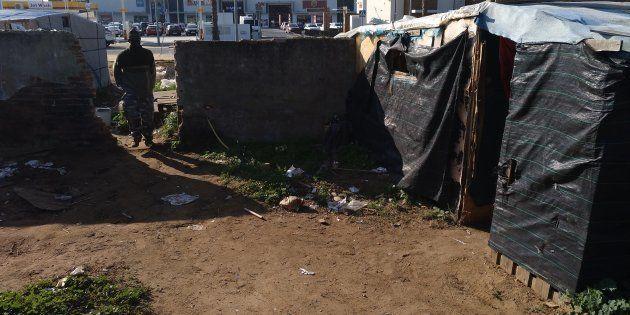 Chabola del asentamiento del cementerio (Lepe) y centro comercial al otro lado de la