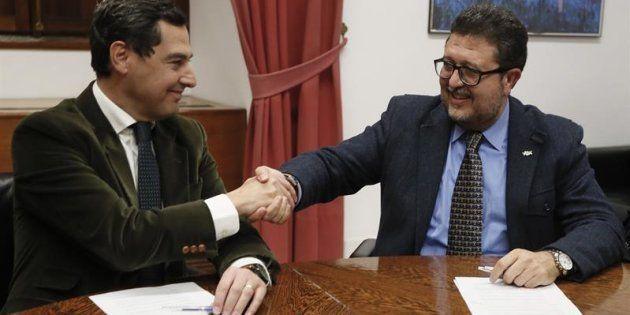El presidente del PP-A, Juanma Moreno (i), estrecha la mano con el líder andaluz de Vox, Francisco Serrano,...