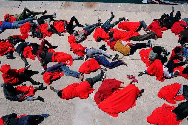 Un grupo de migrantes descansa en el puerto de Tarifa, tras ser rescatados en el