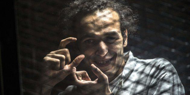 Shawkan, haciendo fotos con sus manos en la zona enrejada desde la que asistía a su juicio, en agosto...