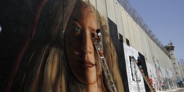El artista italiano Jorit Agoch pinta un retrato de Ahed Tamimi en el muro de separación levantado por...