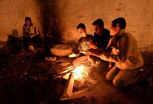 Niños marroquíes sin hogar tratan de calentarse en una hoguera, en