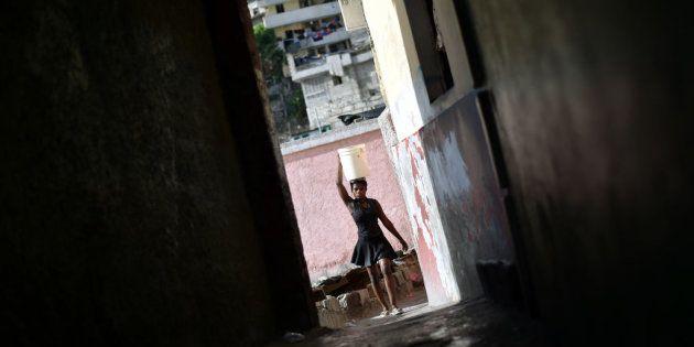 Una mujer lleva un cesto en un callejón de Puerto Príncipe, la capital de