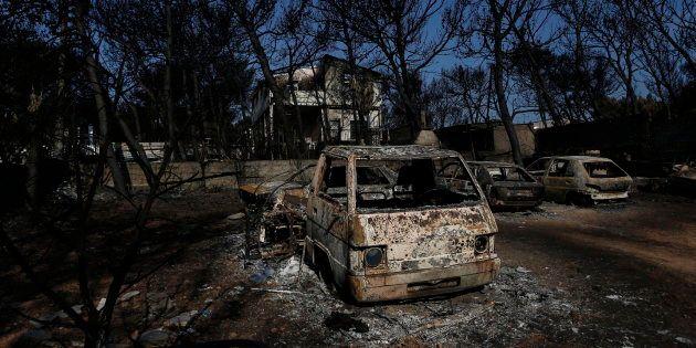 Vehículos destruidos frente a una casa dañada tras el incendio forestal en Mati,