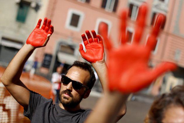 Un grupo de manifestantes, con las manos rojas, protestan contra el racismo de