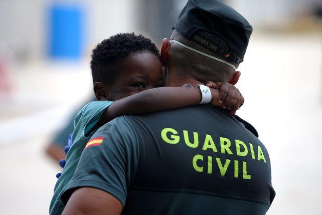 Un niño abraza a un guardia civil en Los Barrios, Cádiz, tras instalarse en el centro de