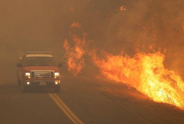 Un camión de bomberos pasa junto a las llamas que se extendieron por una carretera en el Río Fuego (Complejo...