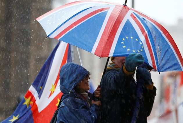 Anti-Brexit protesters shelter from the rain outside the Houses of Parliament, after Prime Minister Theresa...