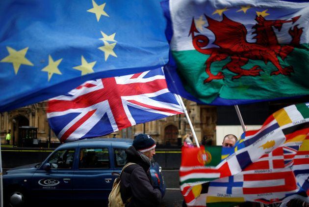 Flags flutter outside the Houses of Parliament, after Prime Minister Theresa May's Brexit deal was rejected,...