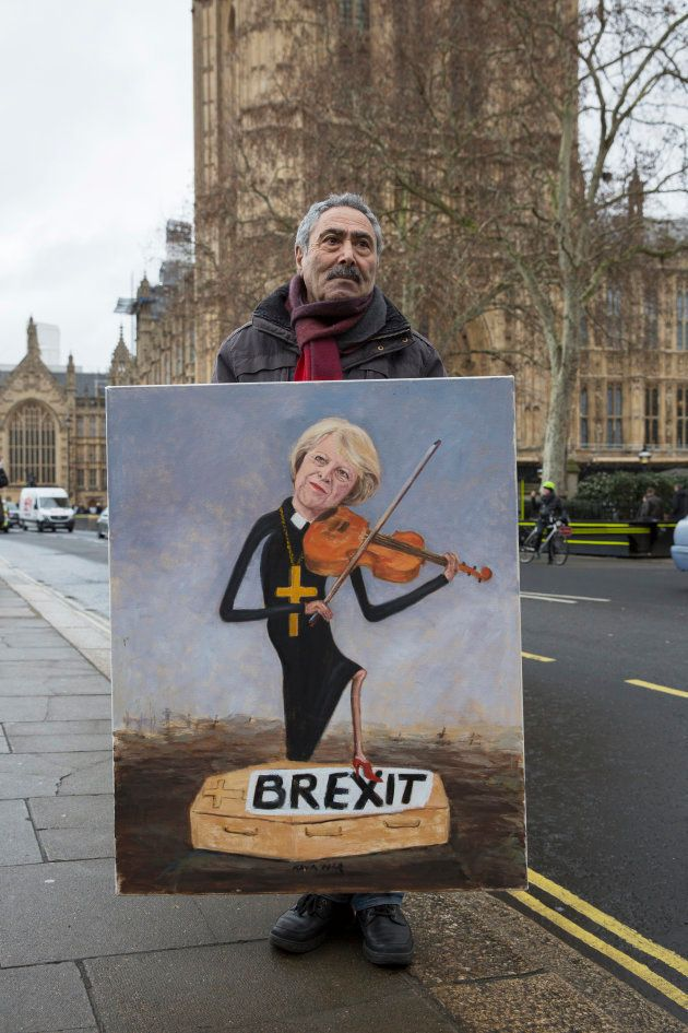 Political satire artist Kaya Mar poses with his artwork of Prime Minister Theresa May playing the violin...