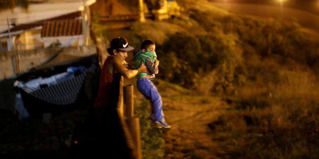 Un migrante de Honduras ayuda a su hijo a cruzar la valla fronteriza entre México y EEUU, en la zona...