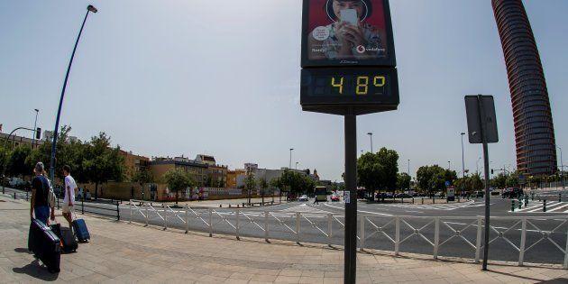 Unos turistas pasan ante un termómetro en Sevilla que marca 48