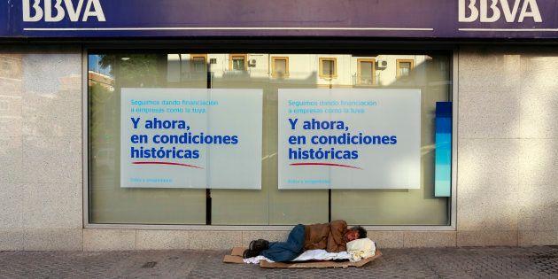Un hombre sin hogar duerme a las puertas de un banco, en