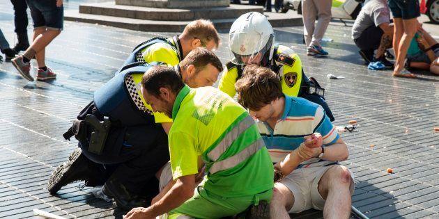 Un grupo de ciudadanos y agentes atiende a una persona herida en el atentado de Barcelona, en La Rambla,...
