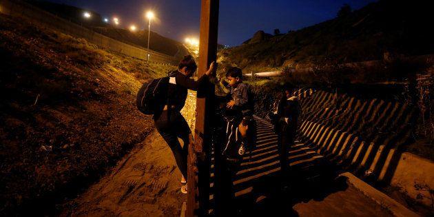 Migrantes de honduras tratan de saltar la valla que separa México y Estados