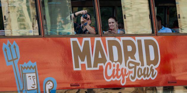 Unos turistas toman fotos de Madrid desde el autobús turístico que recorre el centro de la