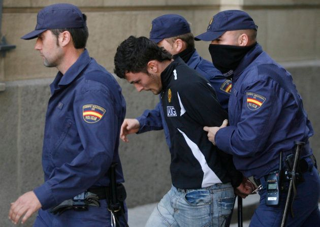 Samuel Benitez (C) is escorted by policemen as he leaves court in Seville March 17, 2009. Benitez was...