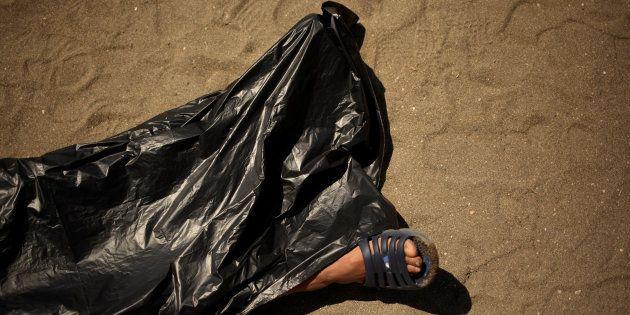 Un activista de Amnistía Internacional posa como un ahogado en una playa de Málaga para denunciar las...
