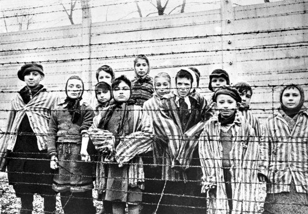 Un grupo de niños supervivientes tras una de las verja en