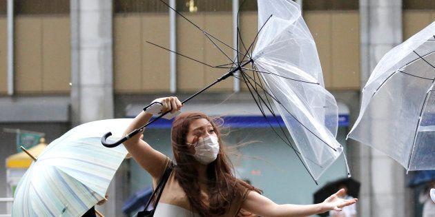Una japonesa pelea contra los fuertes vientos de Shanshan, que le han roto su