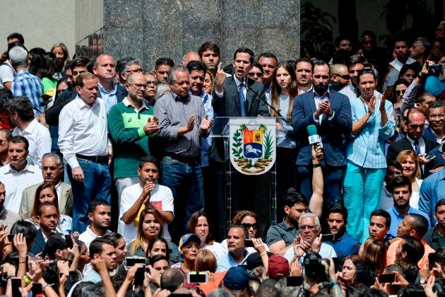 Venezuela's National Assembly head and the country's self-proclaimed 'acting president' Juan Guaido (C),...