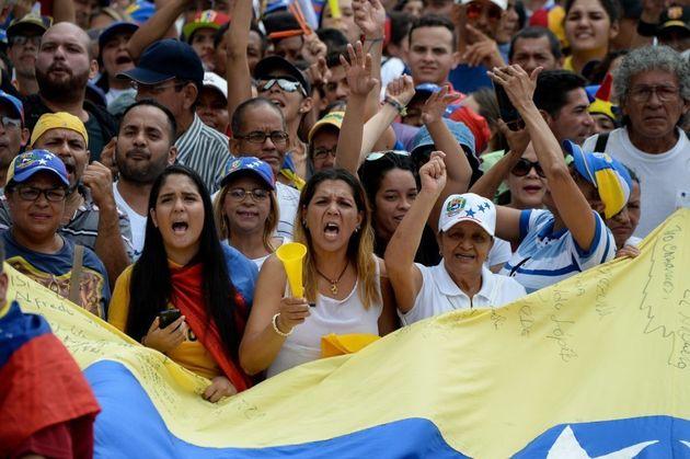 Personas escuchando el discurso de Juan Guaidó, presidente de la Asamblea Nacional de Venezuela.