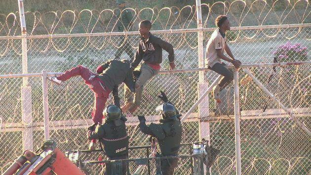 Inmigrantes durante un salto a la valla de Melilla en