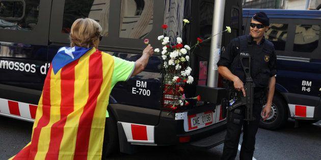 Una mujer con una estelada pone claveles en un vehículo de los Mossos, durante una protesta por el veto...