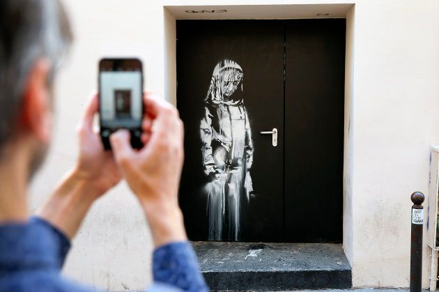 PARIS, FRANCE - JUNE 26: A man takes a picture of a recent artwork attributed to street artist Banksy...