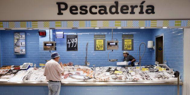 Un hombre compra pescado en la sección de pescadería de una supermercado de la Plaza de Dia en