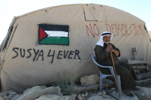 A Palestinian man sits outside his tent in the southern West Bank village of Susya on July 22, 2015....