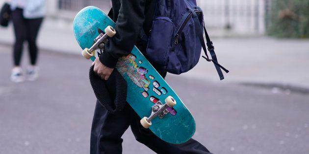 Un joven porta un monopatín, en una imagen de