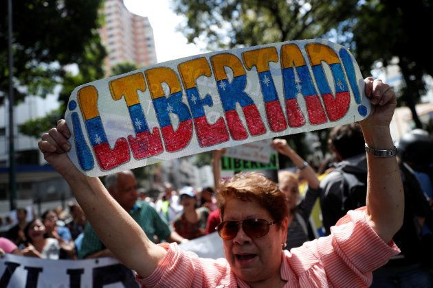 A supporter of Venezuelan opposition leader and self-proclaimed interim president Juan Guaido holds a...
