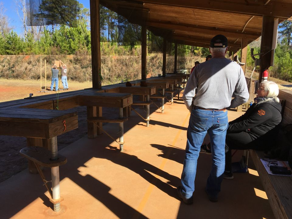 Alguns praticantes de tiro esperam sua vez enquanto outros montam seus alvos durante um cessar-fogo em...