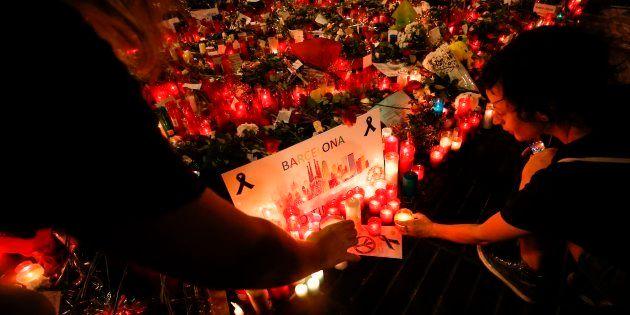 Un grupo de personas coloca carteles y velas en La Rambla de Barcelona, el 22 de agosto de